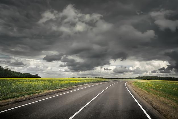 雷雨の前の夏の田舎道。劇的な空。