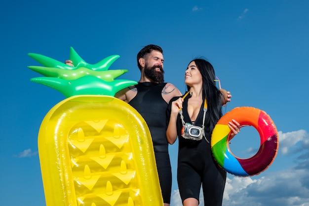 Летний отпуск пары. летнее понятие. человек с надувным матрасом. сексуальная женщина в купальнике.