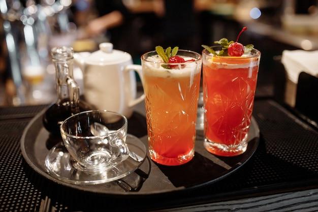 Летний клюквенный лимонад, украшенный мятой и вишней на барной стойке.