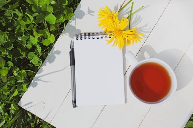夏のかわいいフラットレイアウト:一杯のお茶、空白のページが付いたメモ帳、ペン、白い木製の背景に3つの黄色のヒナギク。側面には新鮮な草です。まばゆい日の光。 copyspace、ミニマリズム。