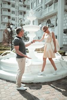 夏の日。暑い夏の日に美しい噴水の近くを歩いて手をつないで幸せなカップル。