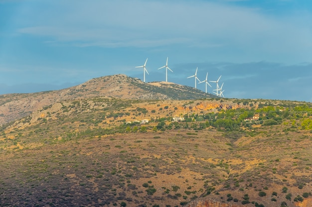 Summer day on the hills in greece. a small village and several wind farms on top of a mountain