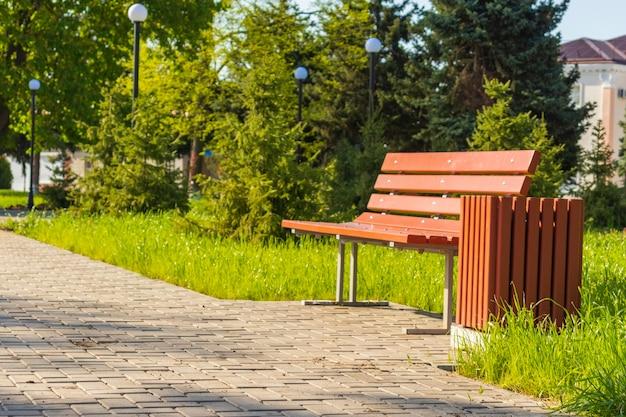 Летний день в общественном городском парке, скамейка и урна