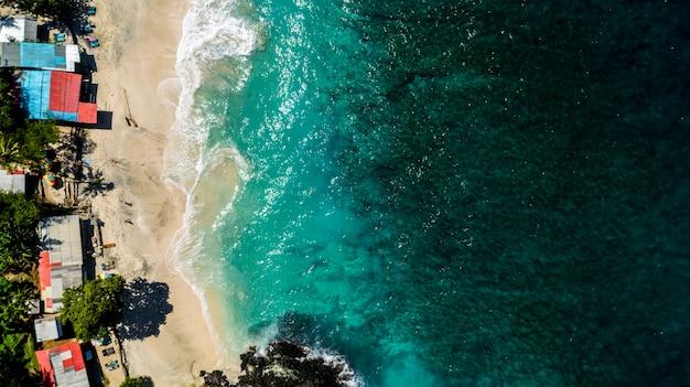オーシャンビューティフルビーチの夏の日。人々は晴れた日に海で入浴します。インドネシア、バリ島の白い砂浜。上面図。