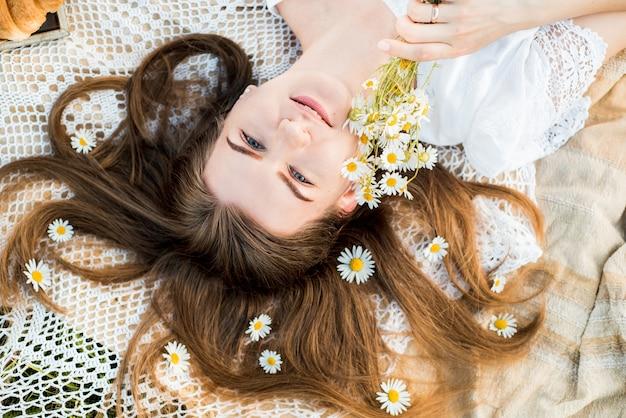 夏の日、村でのピクニック。帽子をかぶった美しい少女が格子縞の格子縞の上に横たわっています。ヒナギクの花束、髪に花。