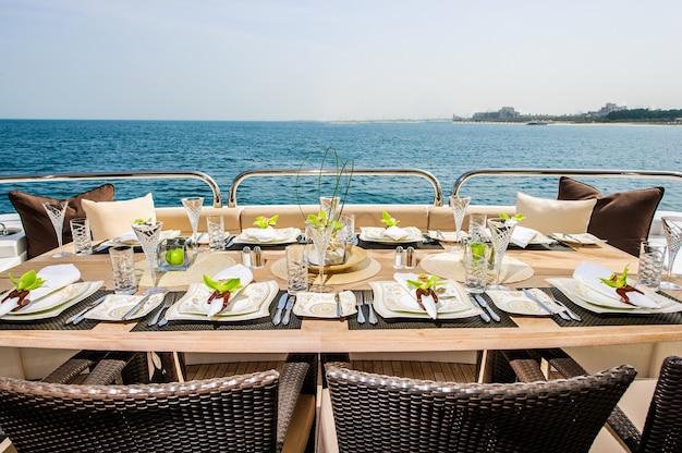 Летняя дневная яхтенная палуба с обслуживаемым столом и открытым морем.