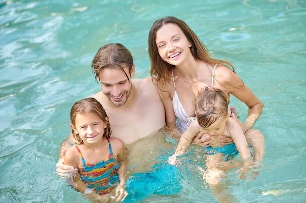 여름날. 여름 수영장에서 시간을 보내는 젊은 가족