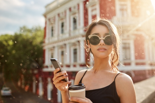 Summer days. close up portrait of attractive skinny feminine caucasian woman with dark hair in tan-glasses and black dress, waiting for boyfriend that being late for date, chatting with friend