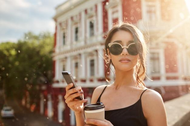 夏の日々。日焼けメガネと黒のドレスで黒い髪の魅力的なスキニーフェミニンな白人女性の肖像画を間近します。デートに遅れているボーイフレンドを待って、友達とチャット