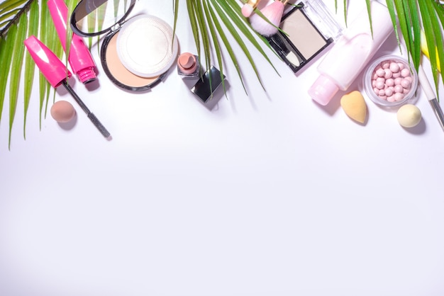 Summer decorative cosmetic set, professional makeup and accessories on white background with palm leaves flatlay top view copy space