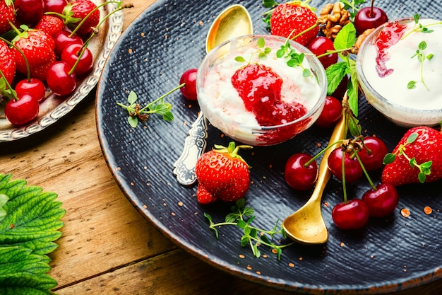Summer dessert, ice cream with strawberries and cherries.ice cream with berry jam on wooden table
