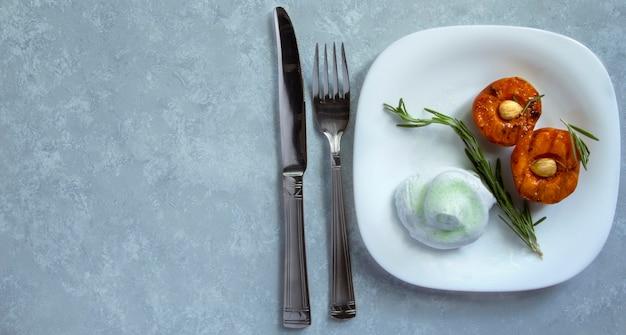 Летний десерт. спелые персики на гриле с ядрами абрикоса и листьями розмарина на белой миске. плоская планировка, копия пространства
