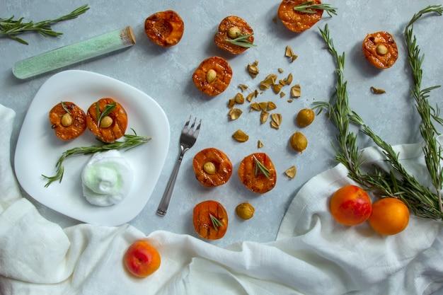 Летний десерт. спелые персики на гриле с ядрами абрикоса и листьями розмарина на белой миске. плоская планировка, вид сверху