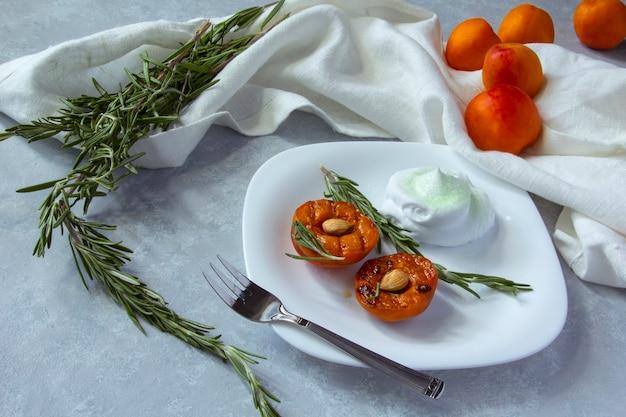 Летний десерт. спелые персики на гриле с ядрами абрикоса и листьями розмарина на белой миске.