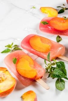 Летние десерты. замороженные напитки. сладкие фруктовые фруктовое мороженое из замороженного персикового чая с мятой. на белом мраморном столе, с ингредиентами персики, мята, лед.