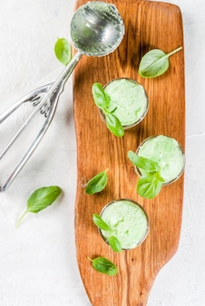 Летние десерты. веганская еда. базиликовое мороженое в сервировочных стаканах, украшенное свежими листьями базилика. на деревянной разделочной доске, на каменном белом столе. вид сверху