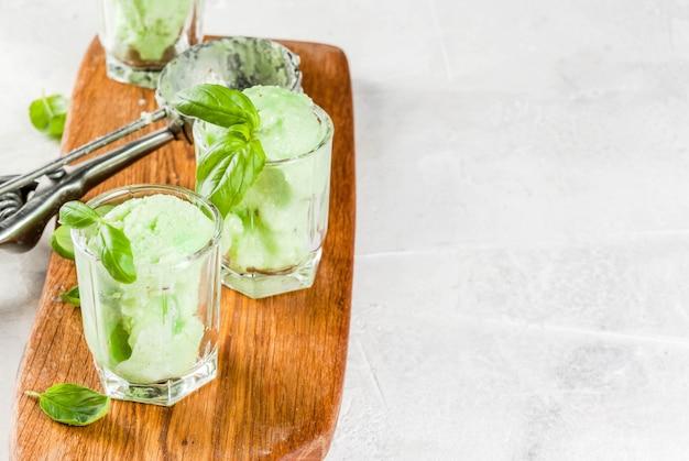 Летние десерты. веганская еда. базиликовое мороженое в сервировочных стаканах, украшенное свежими листьями базилика. на деревянной разделочной доске, на каменном белом столе.
