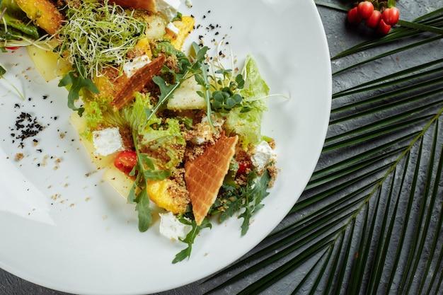 상추, 수박, 복숭아, 페타 치즈 잎을 곁들인 여름 다이어트 샐러드. 밝은 파란색 배경 복사 공간에.
