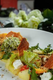水色の背景にレタススイカ桃とフェタチーズの葉と夏のダイエットサラダ