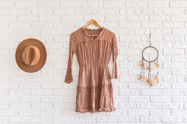 Summer dress, hat and dream catcher hanging on white brick wall background