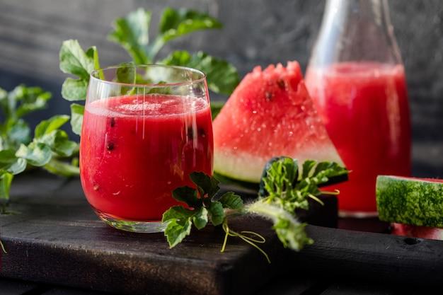 夏の飲み物木の板にライムとミントを入れた冷たいスイカジュースベリーフルーツのスムージー