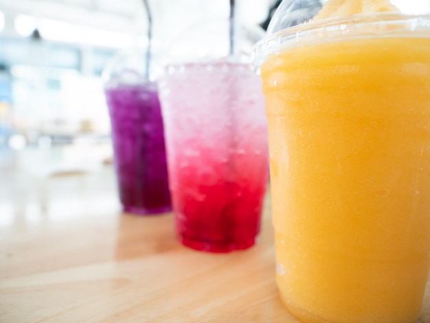 Summer drink in disposable plastic cup and dome cap of mango frappe, strawberry soda and blueberry