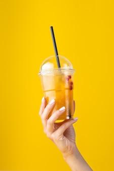 여름 음료 노란색 배경에 플라스틱 컵에 오렌지와 신선한 레모네이드. 유리를 들고 여성 손입니다. 귀하의 광고에 대한 모형. 공간을 복사합니다.