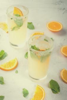 夏の飲み物。明るい灰色の石の大理石のテーブル、選択と集中、トーンのグラスに氷と新鮮なオレンジとミントレモネード