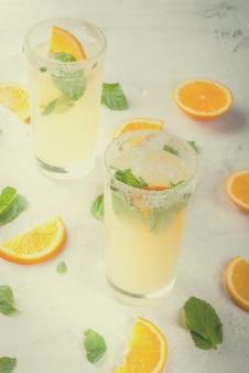 Summer drink. fresh orange and mint lemonade with ice in glasses on light grey stone marble table, selective focus, toned