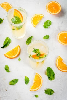 Summer drink. fresh orange and mint lemonade with ice in glasses, light grey stone marble table, selective focus