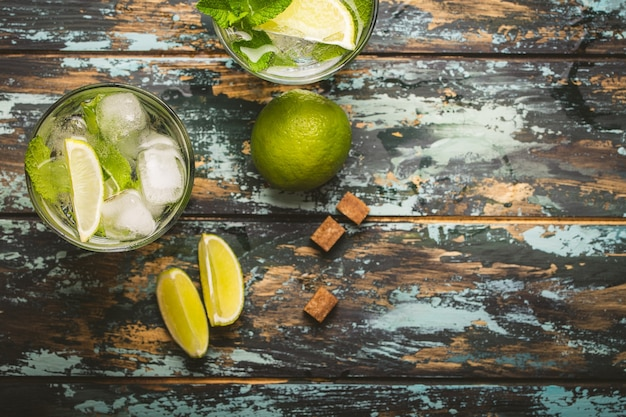 Summer drink in glass and ingredients for making mojito with ice, brown sugar, lime slices, fresh mint on wooden rustic background, space for text. cold refreshing cocktail for summer party and fun
