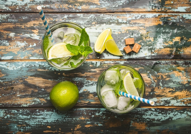 Summer drink in glass and ingredients for making mojito with ice, brown sugar, lime slices, fresh mint on wooden rustic background, top view. cold refreshing cocktail great for summer party and fun