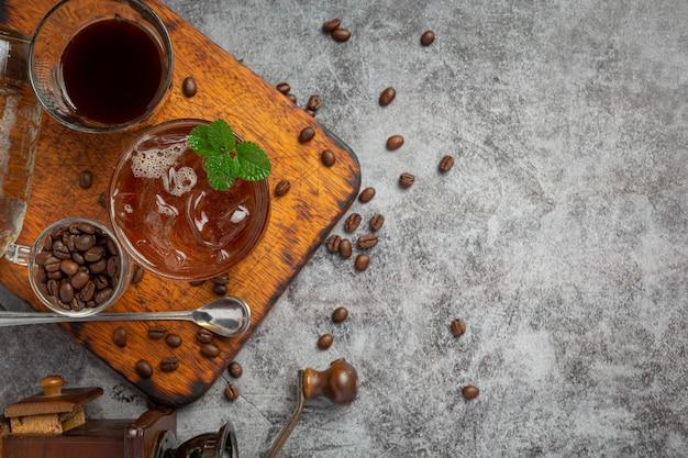 여름은 어두운 표면에 유리 잔에 아이스 커피 또는 소다를 마 십니다.
