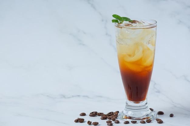 Bevanda estiva caffè ghiacciato o soda in un bicchiere sulla superficie bianca.