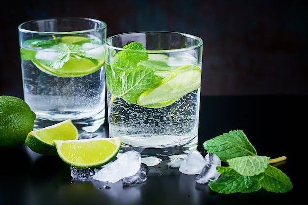 Summer drink lemonade mojito with lime, mint and ice on a black background