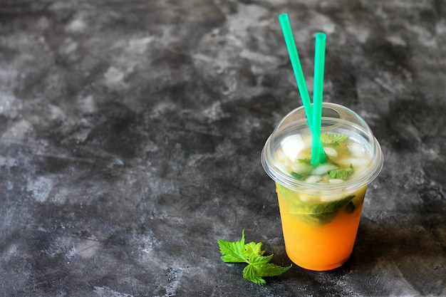 Summer drink lemonade with orange and mint in the plastic cup on a dark background.