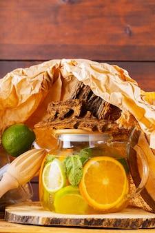 Летний напиток из воды, лимона, апельсина и листьев мяты на деревянных досках. лайм-мятный чай со льдом и кусочки дерева. творческая композиция