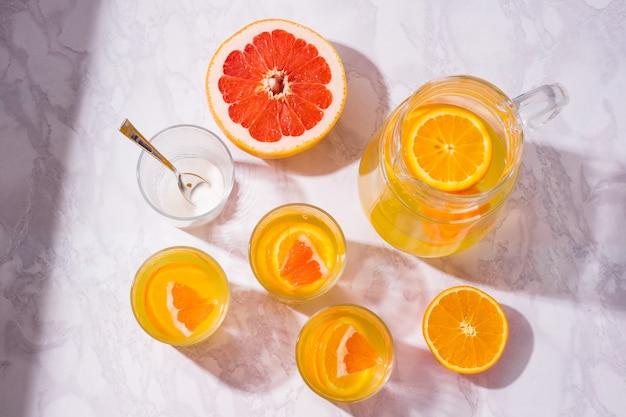 夏の飲み物。オレンジとグレープフルーツのさわやかな飲み物。上面図フラットレイ背景。