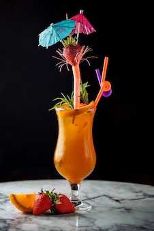 Summer drink orange cocktail with pipes and umbrellas.
