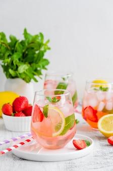 Летний напиток - клубничный лимонад с мятой и кубиками льда в стакане.