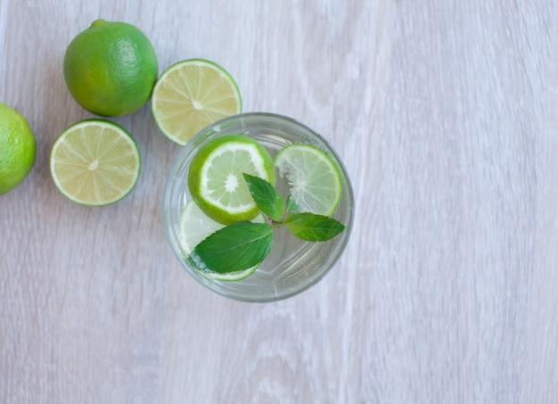 Летний напиток. традиционный лимонад с лимоном, лаймом, мятой и льдом на белом бетонном столе. вид сверху