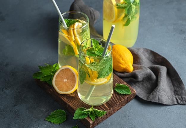 Летний напиток с лимоном и мятой в двух прозрачных стаканах. лимонад. вид сбоку.