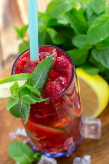 Summer drink with raspberries, lime and ice on a old wooden table