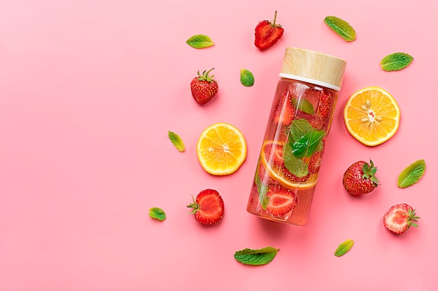 Summer drink with strawberry, lemon, leaf of mint on pink background.