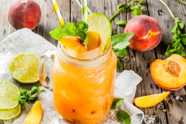 Summer drinks, cocktails. vegan food. peach smoothies, juice or lemonade. in a mason jar, with lime
