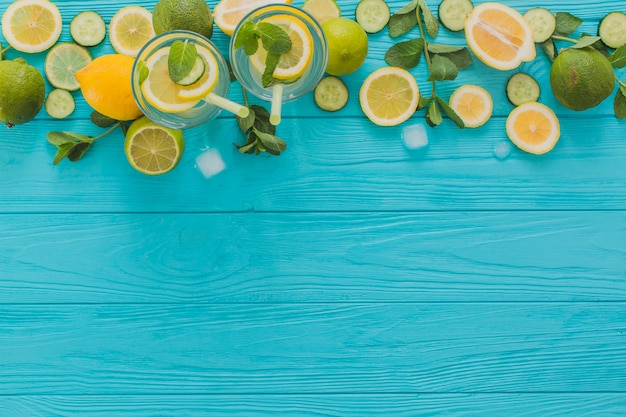 Summer drinks, limes and lemons on wooden surface