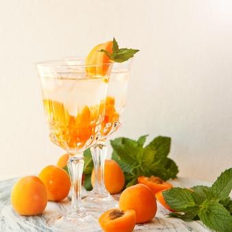 여름 음료, 안경에 얼음을 넣은 민트 살구 칵테일. 상쾌한 여름 홈메이드 알코올 또는 무알코올 칵테일 또는 디톡스 가향 물