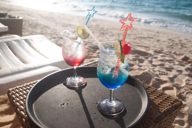 Summer drinks on table and the beach
