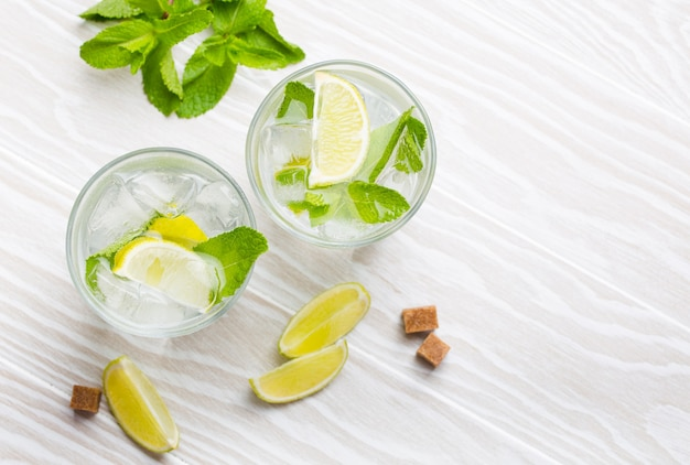 Summer drinks with ice, lime and fresh mint in glasses on white wooden rustic background. top view of cold refreshing lemonades/mojito great for summer party and fun, overhead, closeup