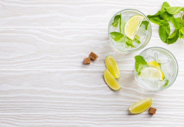 Summer drinks with ice, slices of lime, fresh mint in glasses on white wooden rustic background, space for text. cold refreshing lemonades/mojito great for summer party and fun, copy space, top view
